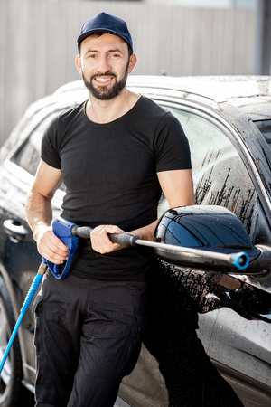 Portrait of a professional washer in black t-shirt and hat standing near the car outdoors