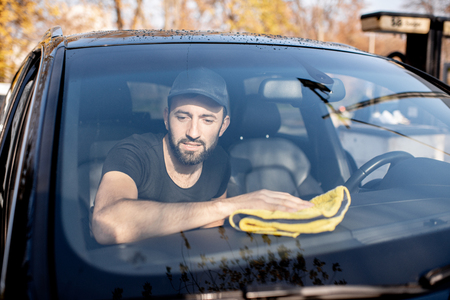Professional washer wiping car panels with yellow microfiber, view through the windshield Stockfoto