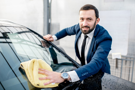 Smiling businessman dressed in a suit wiping windshield of his car with yellow microfiber on a self service car wash outdoors
