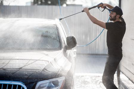 Professional washer in black uniform washing luxury car with water gun on an open air car wash