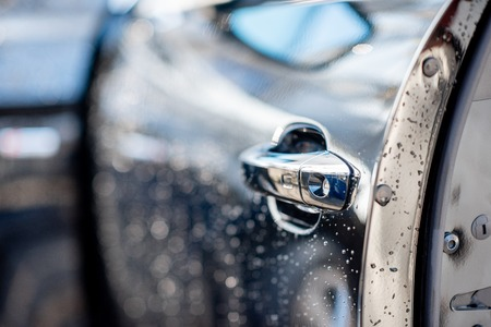 Close-up of a door handle of a washed car outdoors