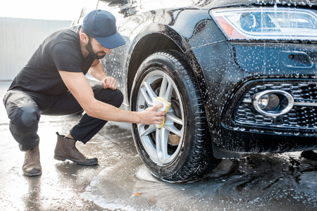 Professional washer in black uniform and cap wiping with sponge car wheel during the washing process outdoors Фото со стока