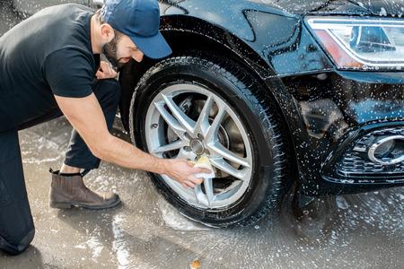 Lavadora profesional en uniforme negro y gorra limpiando con esponja la rueda del coche durante el proceso de lavado al aire libre
