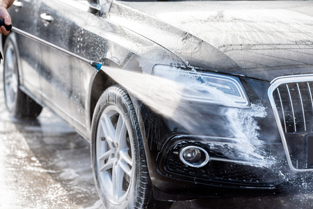 Close-up of a car under the water jet during the washing process on a self service car wash Stock Photo