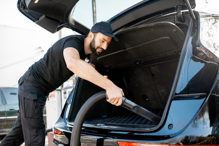 Professional cleaner in black t-shirt and cap vacuuming trunk of a luxury big car outdoors