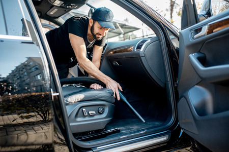 Professional cleaner in black t-shirt and cap vacuuming leather seats of a luxury car