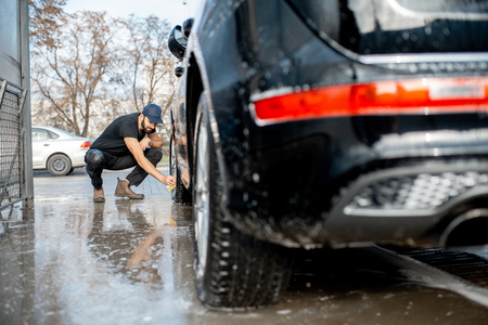 Professional washer in black uniform and cap wiping with sponge car wheel of a luxury car during the washing process outdoors