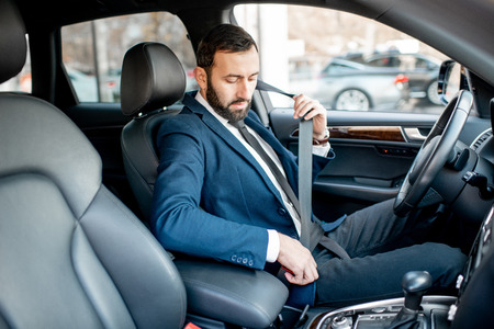 Elegant businessman dressed in the suit fastening the safe belt before driving his car