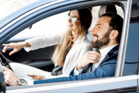 Elegant businessman tightening the tie while driving a car with businesswoman
