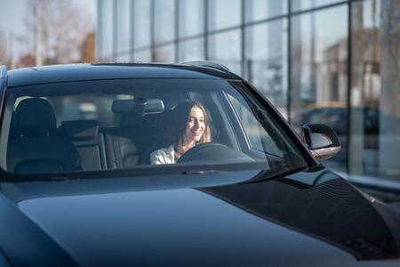Jeune femme d'affaires conduisant une voiture de luxe, vue de l'extérieur à travers le pare-brise
