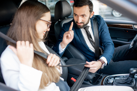 Businesman fastening belt to a woman worrying about her safety in the car