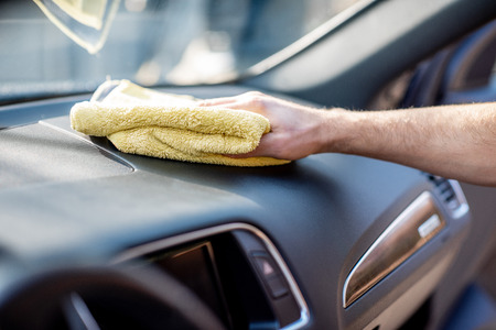 Wiping panel of a luxury car with yellow microfiber, close-up view Stock Photo