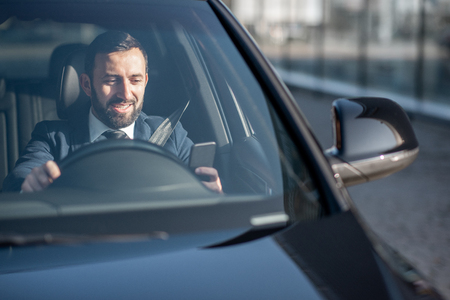 Happy businessman driving a luxury car, view from the outside through the windshield