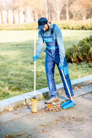 Professional sweeper in uniform sweeping leaves with broom and scoop on the street Standard-Bild