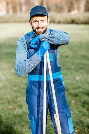 Portrait of a male sweeper in uniform with working tools outdoors