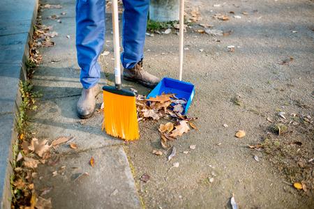 Hombre barriendo hojas con escoba naranja a la pala en la calle, vista cercana sin rostro
