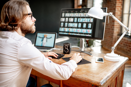 Young male photographer working with womans portraits sitting at the working place with two computers in the studio