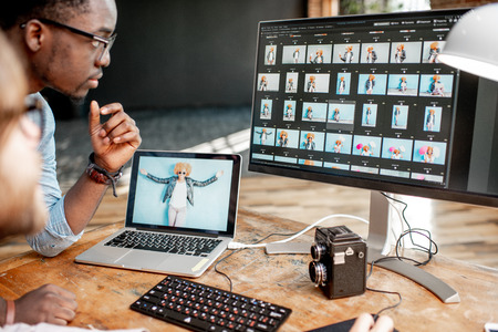 Two male photographers choosing womans portraits at the working place with two computers in the studio Stock Photo