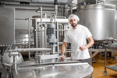 Portrait of a handsome worker in uniform near the stainless tank full with fermenting milk at the cheese manufacturing Stock Photo