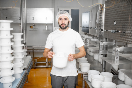Portrait of a man in uniform forming cheese into the plastic molds putting them under the press at the cheese manufacturing