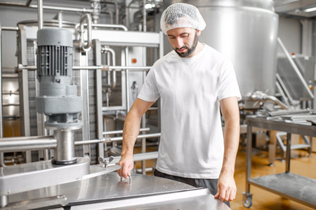 Portrait of a handsome worker in uniform near the stainless tank full with fermenting milk at the cheese manufacturing Stok Fotoğraf