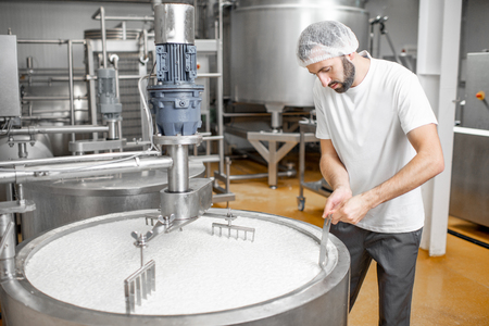 Man mixing milk in the stainless tank during the fermentation process at the cheese manufacturing Banco de Imagens