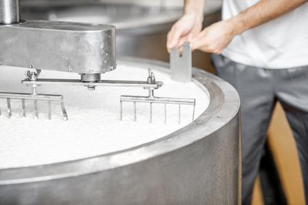 Uomo che mescola il latte nel serbatoio inossidabile durante il processo di fermentazione presso la produzione del formaggio. Vista ravvicinata senza volto