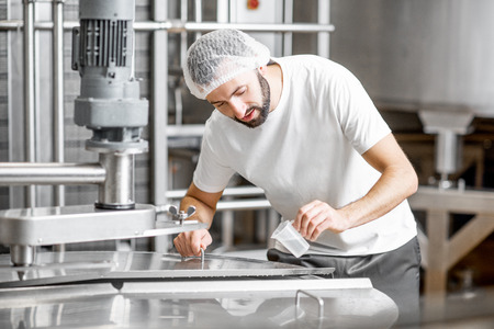 Worker adding supplements during the milk fermentation process in the stainless tank at the cheese manufacturing