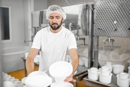 Man in uniform forming cheese into the plastic molds putting them under the press at the cheese manufacturing