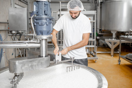 Man mixing milk in the stainless tank during the fermentation process at the cheese manufacturing Stock fotó