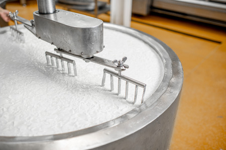 Milk mixing in the stainless tank during the fermentation process at the cheese manufacturing Stok Fotoğraf