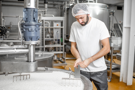 Man mixing milk in the stainless tank during the fermentation process at the cheese manufacturing Stok Fotoğraf