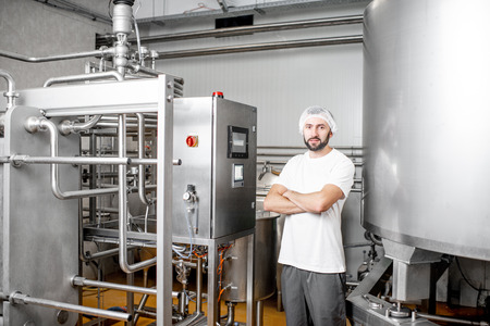 Portrait of a handsome worker operating pasteurizer using the control panel at the cheese or milk manufacturing