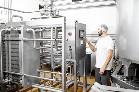 Pasteurizador de funcionamiento del trabajador mediante el panel de control en la fabricación de queso o leche Foto de archivo