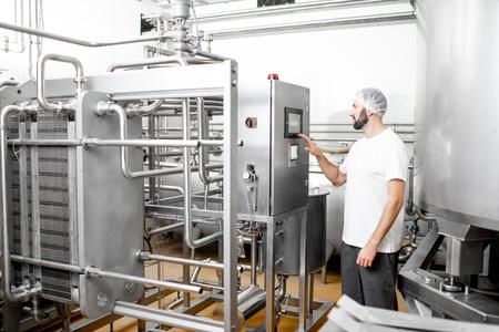 Werknemer die pasteur bedient met behulp van het bedieningspaneel bij de kaas- of melkproductie Stockfoto