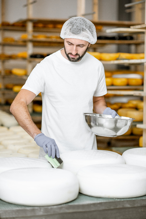Man rubing cheese wheels with wax at the cheese manufacturing with shelves full of cheese on the background 版權商用圖片