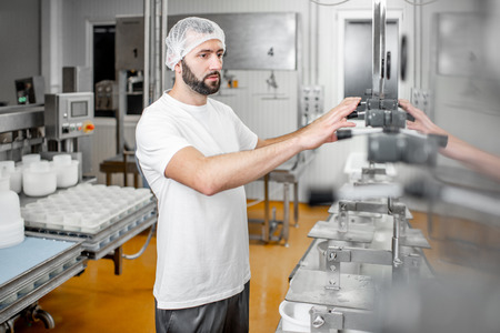 Worker operating press machine pressing cheese at the manufacturing
