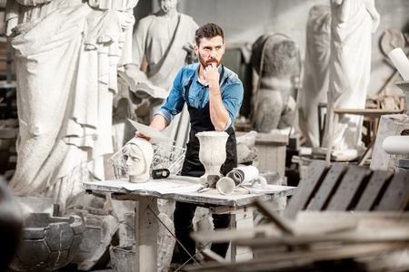 Portrait of a handsome thoughtful sculptor in blue t-shirt and apron working with stone sculptures on the table at the old atmospheric studio Stock Photo