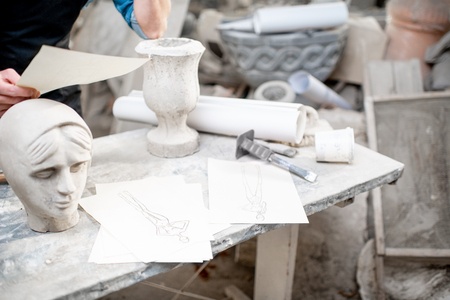 Old working space of the sculptor with stone sculptures drawings and working tools indoors Stock Photo