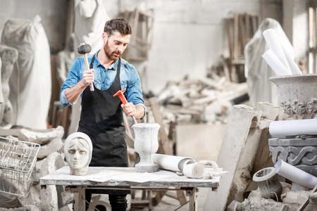 Ritratto di un bel scultore in maglietta blu e grembiule che lavora con sculture in pietra sul tavolo del vecchio studio atmosferico Archivio Fotografico