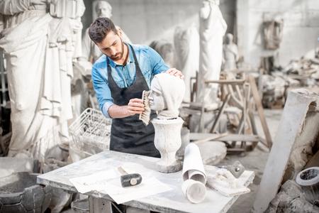 Knappe beeldhouwer borstelt stenen hoofdsculptuur op tafel in de sfeervolle studio