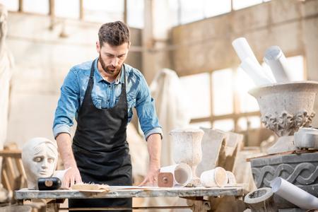 Portret van een knappe mannelijke beeldhouwer op de werkplek in het oude sfeervolle atelier met sculpturen op de achtergrond