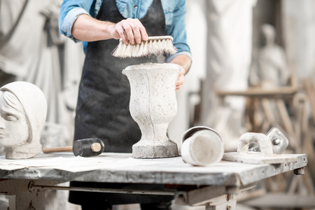Man working with stone vase at the working place in the old studio. Close-up view with no face Stock Photo