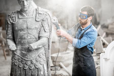 Scultore in scultura di pietra per la macinazione di utensili da lavoro protettivi con smerigliatrice elettrica nel vecchio studio con polvere
