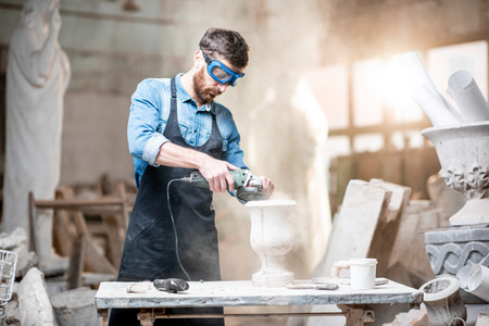 Beeldhouwer in werkgerei slijpstenen vaas bij de werkruimte in het oude sfeervolle atelier