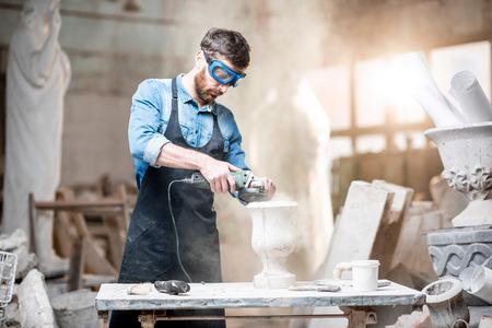 Rzeźbiarz w wyrobach roboczych szlifuje kamienny wazon w miejscu pracy w starej pracowni klimatycznej