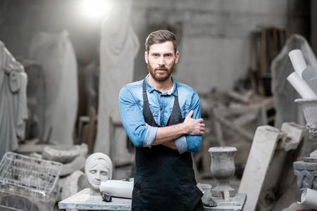 Ritratto di uno scultore bello in maglietta blu e grembiule in piedi in studio con vecchie sculture sullo sfondo Archivio Fotografico