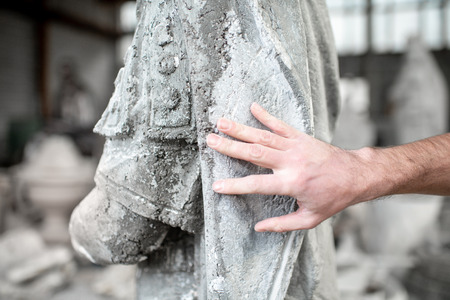 Sculptor touching the old stone sculpture in the studio, close-up view