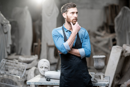 Portrait of a handsomme sculptor in blue t-shirt and apron standing in the studio with old sculptures on the background