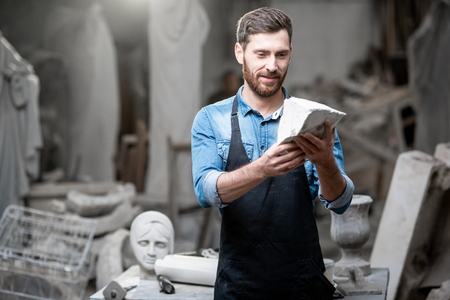 Portrait of a handsome sculptor in blue t-shirt and apron holding a piece of stone in the studio